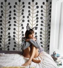 Woman wearing bunny ears sitting on bed, hugging knees, looking away