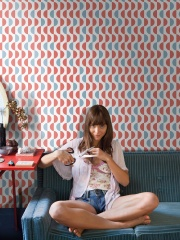 Woman sitting on sofa, cutting hair with scissors, portrait